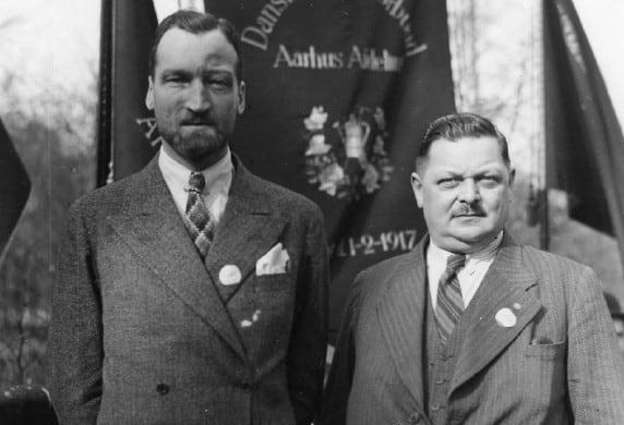 Hartvig Frisch (til venstre) til 1. maj i Friheden i Aarhus, 1937. Han står sammen med forretningsfører Th. Clausen. Som ung blev Frisch opereret for pandehulebetændelse og fik et markant ar i panden. Foto: Den Gamle By.