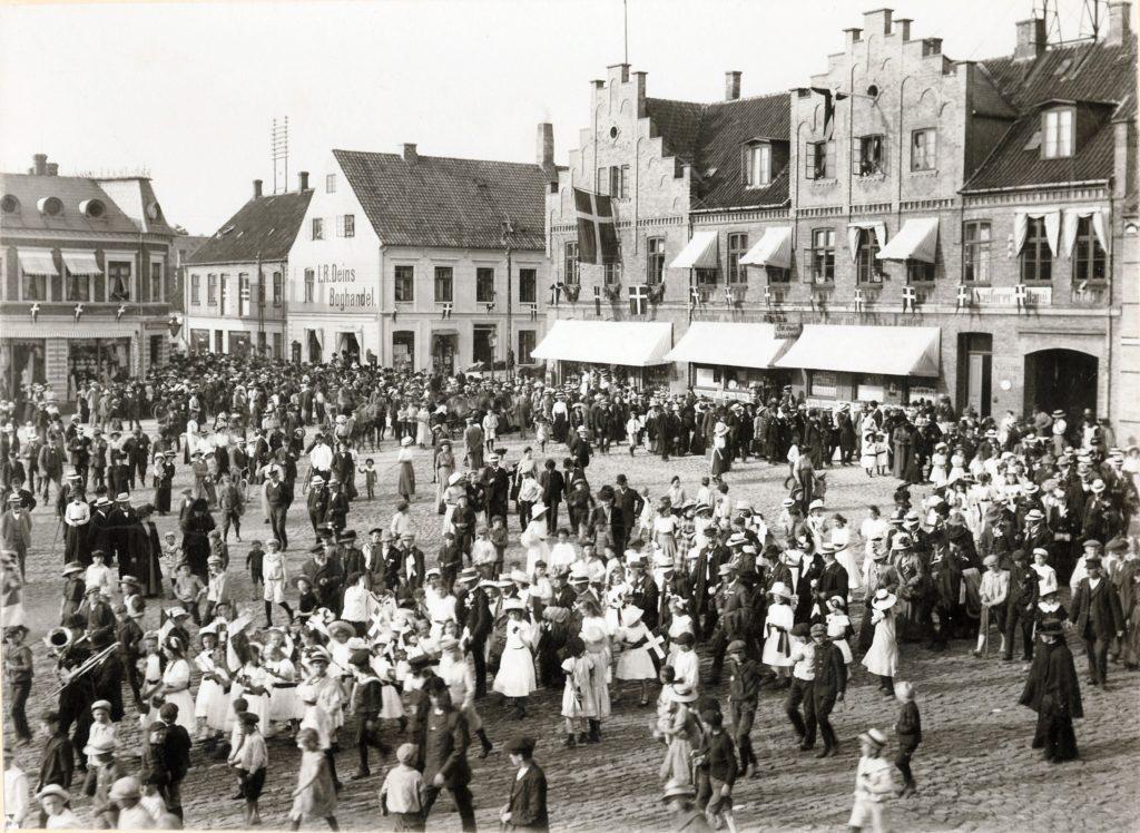 Sønderjysk Forening Billede af den imponerende mængde mennesker på Maribo Torv ved Sønderjydernes besøg 22 til 24.juni 1912. De 100 sønderjyder besøgte sammen med de lokale arrangører bl.a. Borgø og spiste i Aktiehaven.